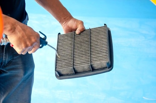 Men are using the blower to clean the air filter car.