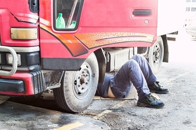 Mechanic under truck repairing dirty greasy oily engine with problem.